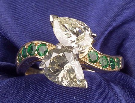 18kt Gold, Diamond and Emerald Twin-stone Ring, prong-set with two pear-cut diamonds, each weighing approx. 1.00 cts., flanked by emerald melee shoulders