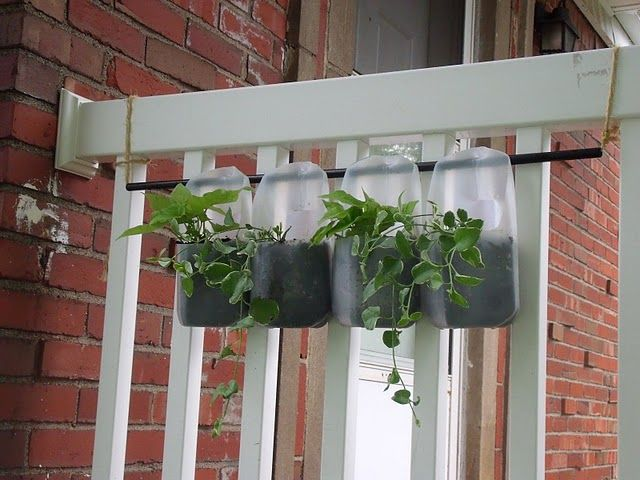 Homemade flower 'box' out of milk cartons, metal rod from a broken laundry hamper, and some rope found in the basement