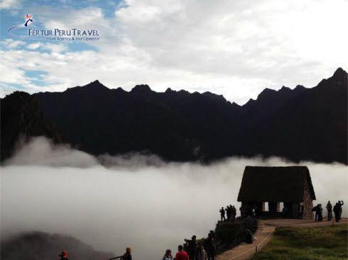 Fast moving shroud of fog wafts through Machu Picchu ruins