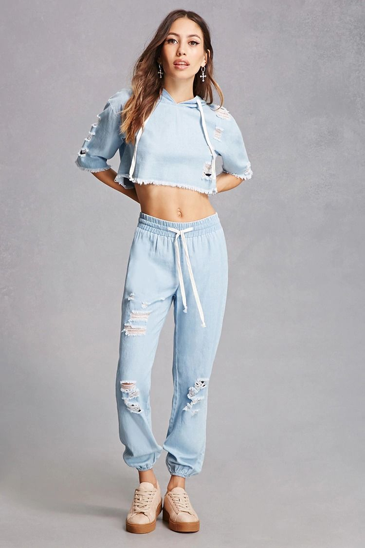 9bbb63e7cf176 A distressed denim set featuring a crop top with a drawstring hood, short  sleeves, and frayed trim, as well as a pair of joggers featuring an  elasticized ...