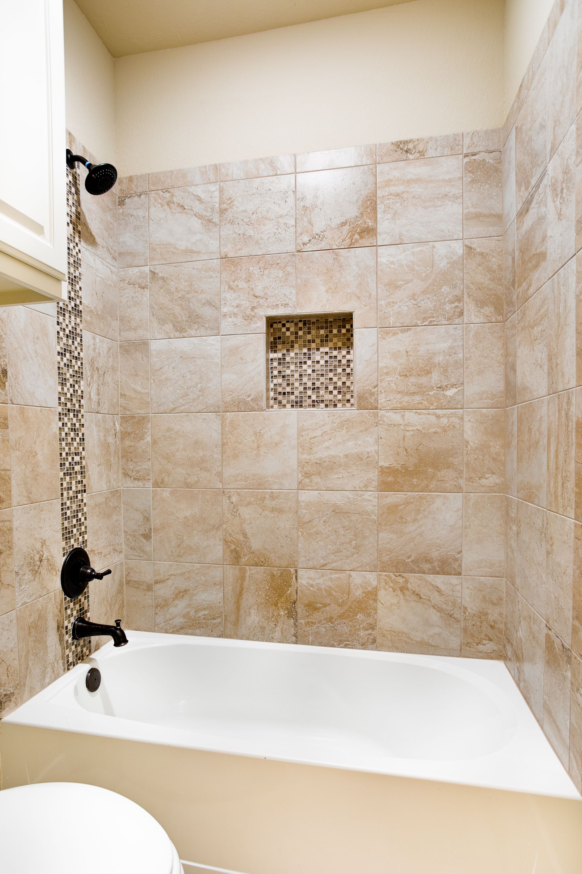 Traditional guest bathroom with tile tub surround, deco ...