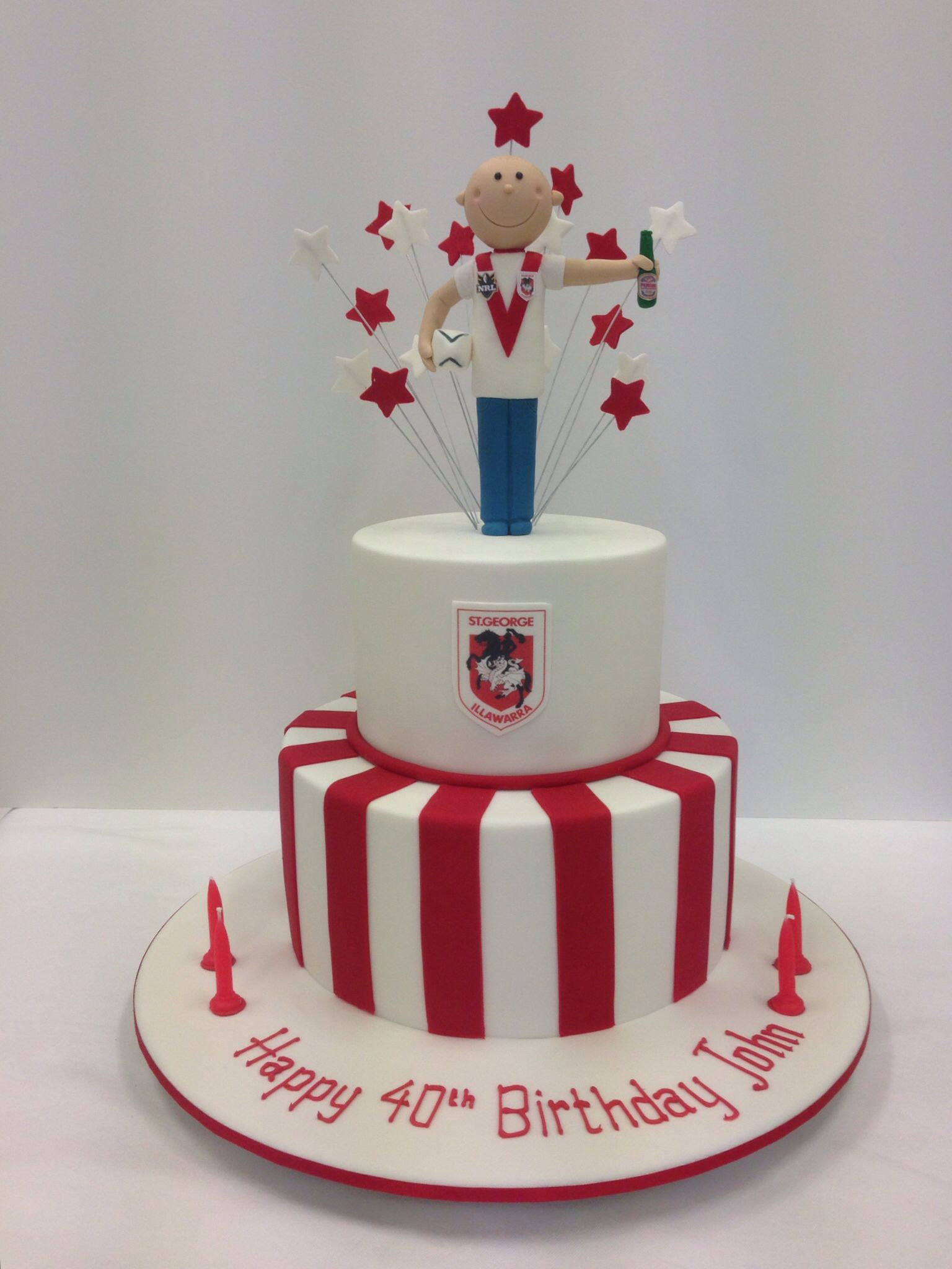 Simple elegant red and white cake with figurines by handis cakes
