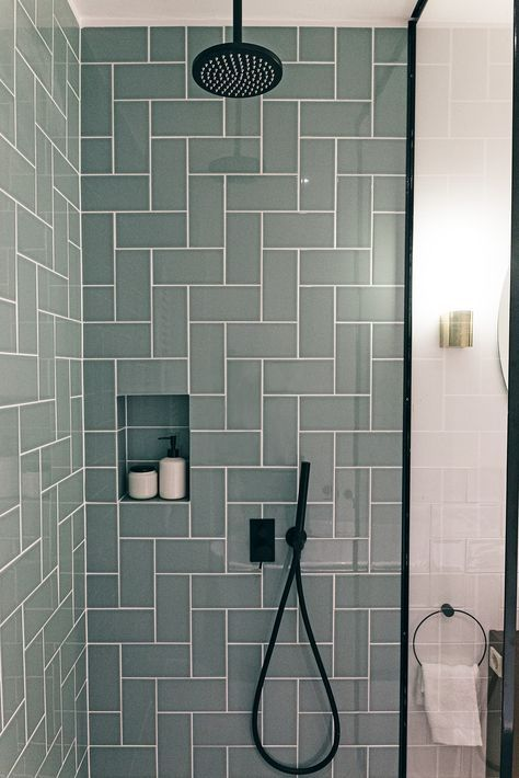 Photo of Contemporary bathroom with black faucets, tiles in a herringbone pattern. Rain a…