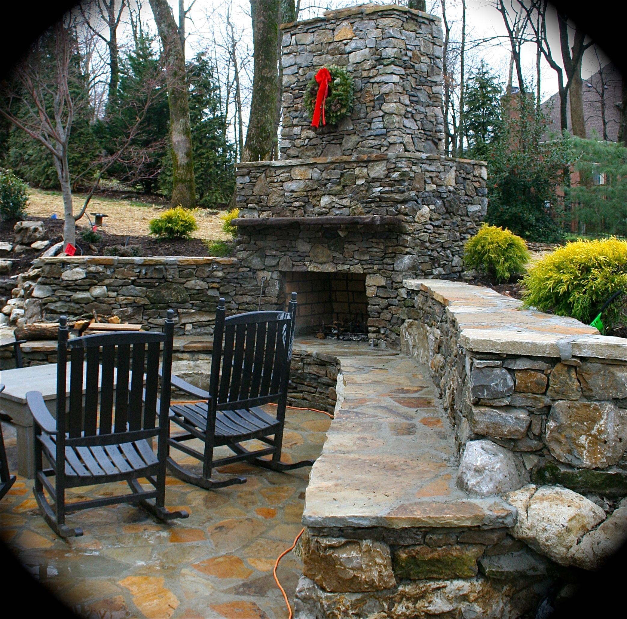 Fireplace seating wall and stone patio Landscaping by Eden