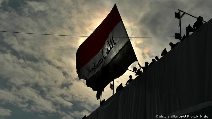 Anti Government Protesters Wave A Flag While Standing On A Building Near Tahrir Square During Ongoing Protests In Baghdad Iraq Baghdad Iraqi