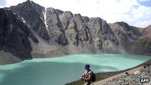 Tourist walks along banks of Lake Ala-Kul, in mountains of Kyrgyzstan