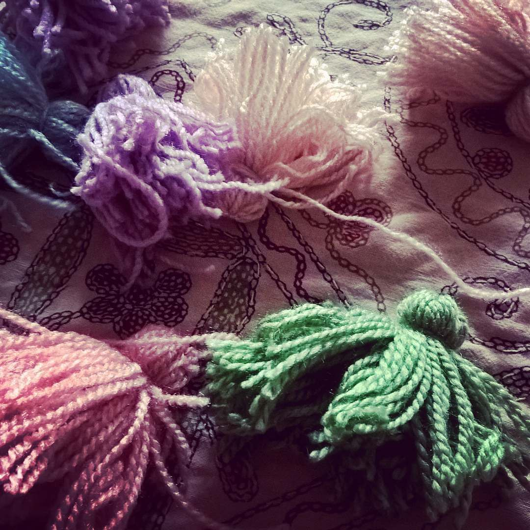 summer vacation means loads of time to kill for the kids...and for us mommies it means time to be a diy diva.   leftover wool being turned into wooly tassles... no purpose. just keeping the lil one busy someties invention is he necessity of a mother  #family #summer #vacations #diy #kids #amomsgottadowhatamomsgottado #daughters #tassles