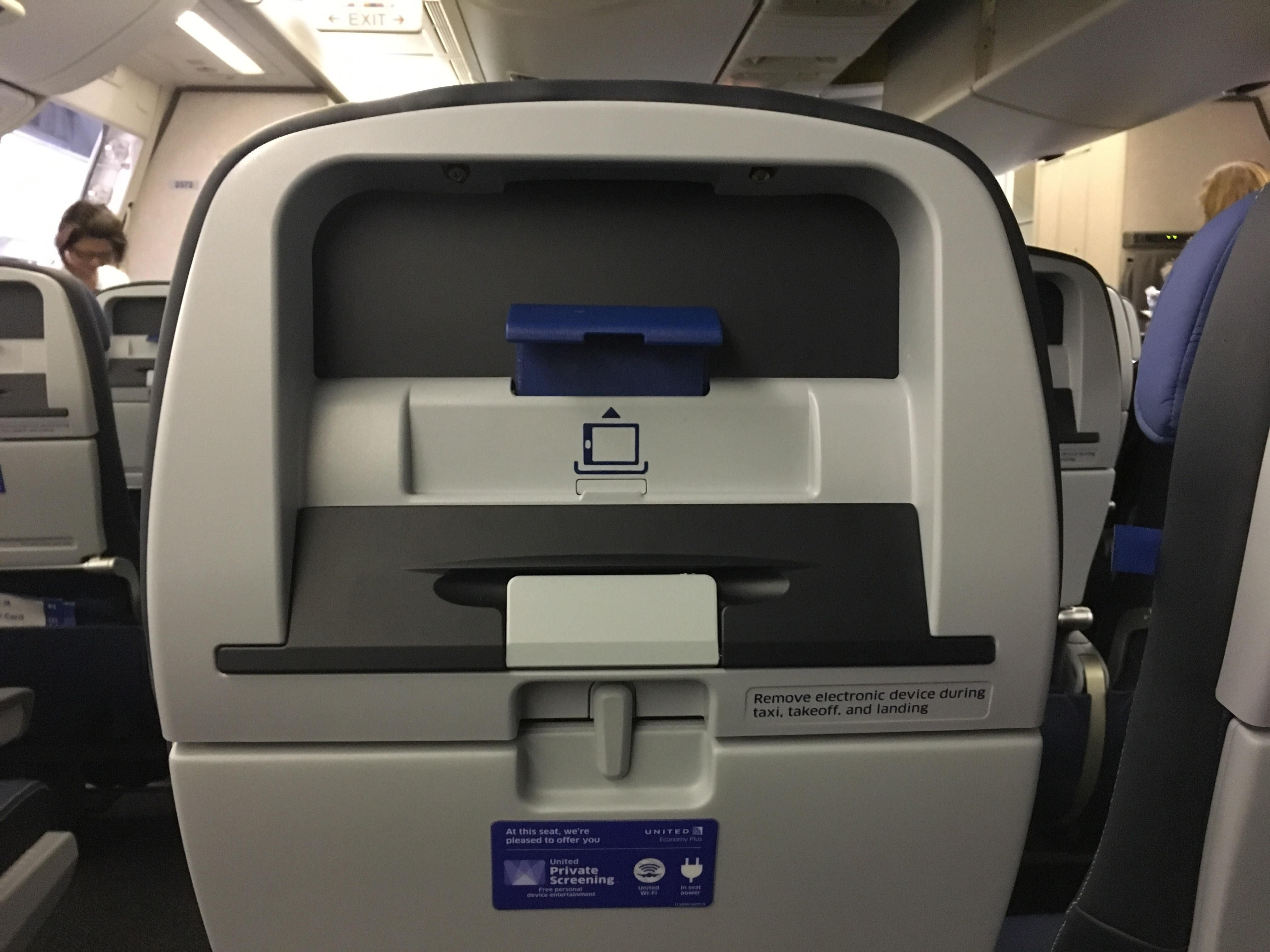 These airplane seats have a holder for your phone or