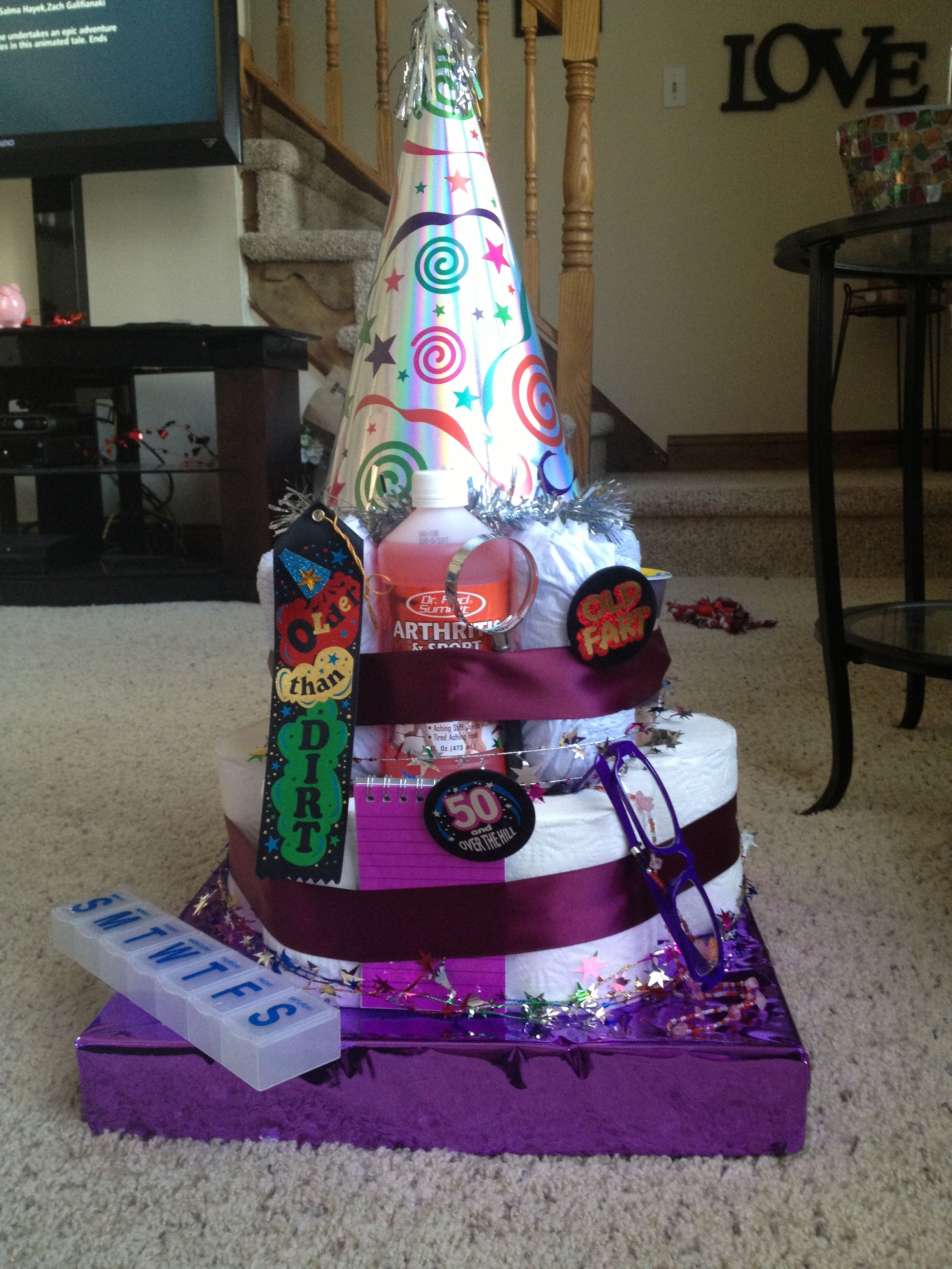 50th Birthday Diaper cake! Dollar store items, adult diapers, toilet paper rolls and paper towel roll in the middle on top of a box wrapped in wrapping paper.