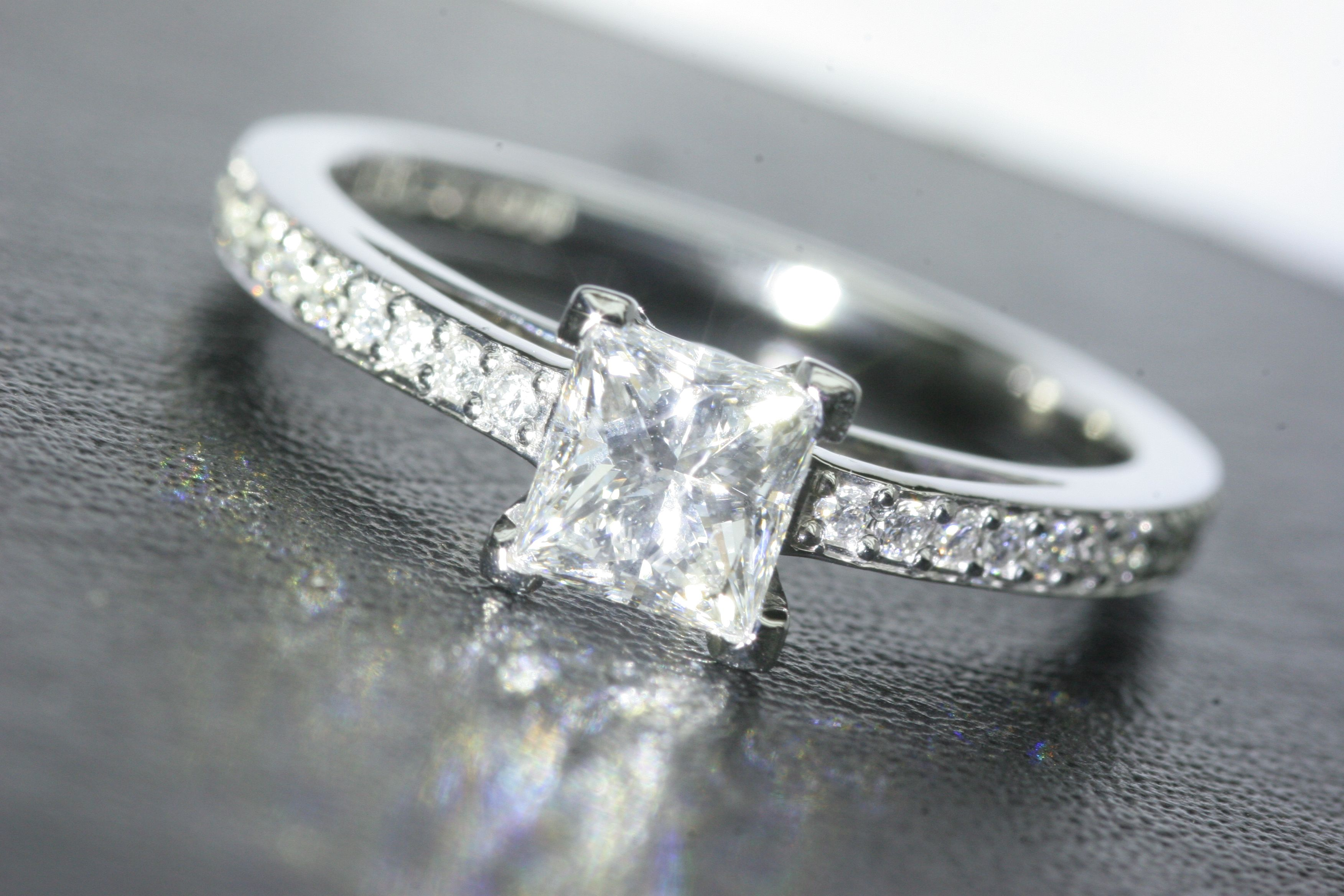 Platinum princess cut diamond solitaire ring set with shoulder
