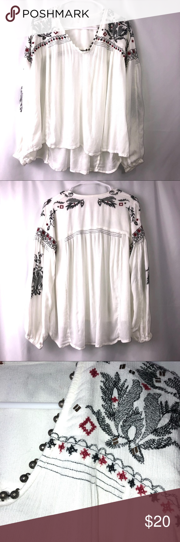"""FREE PEOPLE WHITE BOHO PEASANT TOP EMBROIDERY SZ S Black and red embroidery looks so pretty on this boho peasant top. A few spangles are sprinkled on shoulders and adorable tiny metal balls act as """"buttons"""" on the v-neck. One metal ball is missing. Button loops on other side. Puffy peasant sleeves are also embroidered. VGUC due to missing button. Music festival ready. Armpit to armpit: 22"""" Hips: 24"""" Shoulder to hem: 22"""" Measurements are approximate 0137 Free People Tops Blouses"""