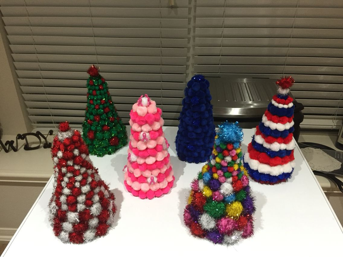 Pom Pom Christmas trees using cone shaped styrofoam forms. Blue for a police officer, pink for breast cancer awareness and red, white and blue for my retired marine friend.