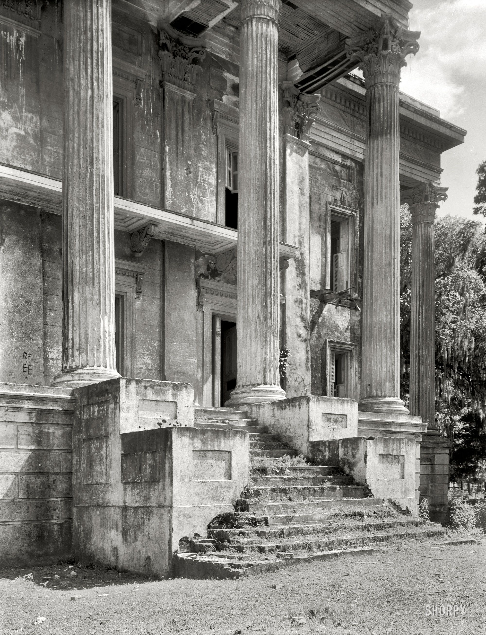 "Iberville Parish, Louisiana. ""Belle Grove. Vicinity of White Castle. Greek Revival mansion of 75 rooms. Ruinous condition. Built 1857 by John Andrews, who sold it to Stone Ware. Occupied by Ware family until circa 1913."" The decaying portico of what was reputedly the largest plantation home in the South."