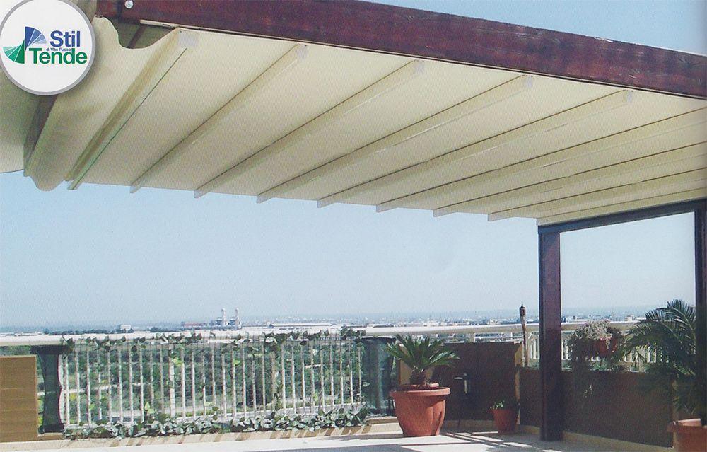 Tenda addossata a parete, richiudibile ad impacchettamento con scorrimento orizzontale, struttura in alluminio rivestito, con travi in legno lamellare di pino impregnato in autoclave.