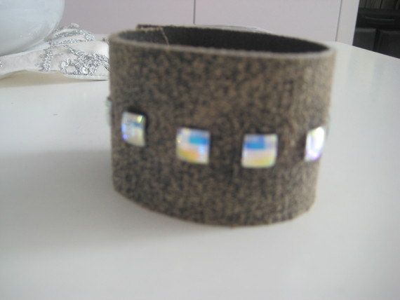 Nataly Noama Quad-Line Swarovski Leather Bracelet: A style that is becoming increasingly popular, this wide leather bracelet is made to light up a room with the camel-colored, quad-line Swarovski crystals. Simplicity does not imply dullness. This piece is versatile.