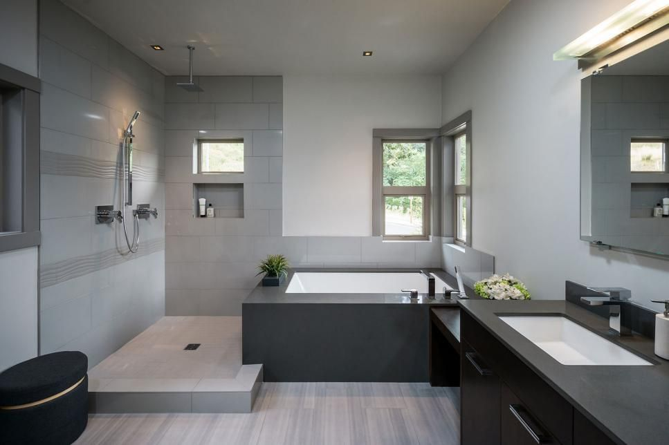 The contemporary gray bathroom features an open shower with accents of wavy gray tile, rainfall showerhead and even a small window for natural light. A large soaker tub sits in the corner with views of the landscape.