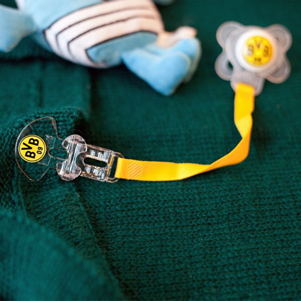 A cute pacifier ribbon which is black and yellow with a clip for easy attachment to clothing.  The ribbon is suitable for every pacifier and thanks to the clip the pacifier is always clean and to hand.  The ribbon features the BVB mascot bee Emma. EN http://www.bvbfanshop.com/stores/bvb/en/product/bvb-pacifier-ribbon/150980 DE https://shop.bvb.de/artikel/BVB-Schnullerband-10261200?utm_source=pinterest&utm_medium=pin&utm_campaign=10261200