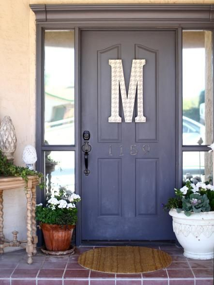 """If you're going to paint your front door, why not go all out? Lifestyle blogger Jill McKee, who dishes on DIY home decor at meandjilly.blogspot.com, gave her door a much-needed makeover with a strip of crown molding and a can of Benjamin Moore paint (color: Iron Mountain). Then she took it up a notch by painting a houndstooth pattern on a papier-mache """"M"""" from a craft store in a lighter shade of gray, distressing it with sandpaper and attaching it to the door to achieve the final look."""