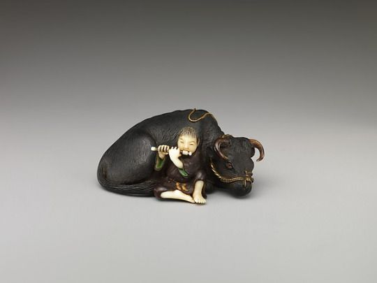 A netsuke figure of a boy playing a flute and an ox. This figure is made of ivory and wood and is currently in the collection of the Metropolitan Museum of Art in New York City.