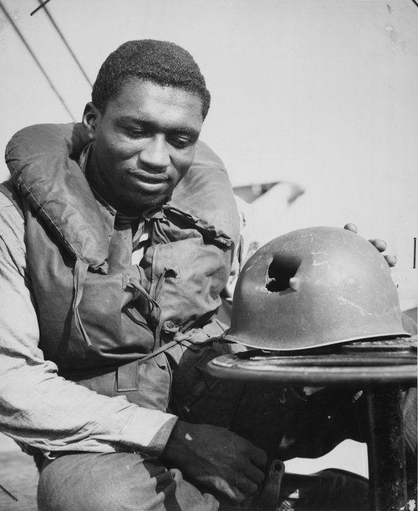 Un soldado de la guardia Costera inspecciona el casco, golpeado por una bala en el sur de Francia . 1940