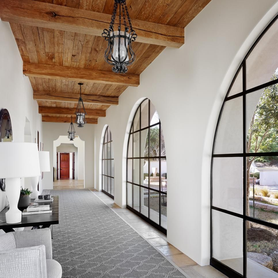 A row of large steel windows illuminate this romantic stretch of hallway and highlight the great view. Warm, natural wood brings its rustic feel from above while clean surfaces and modern design sit below.