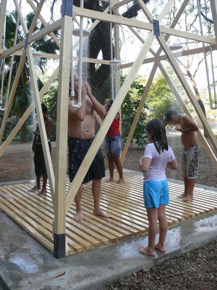 público se refresca do calor intenso nas 4 duchas da torre externa de 10 metros que compõe a instalação da artista nydia negromonte.