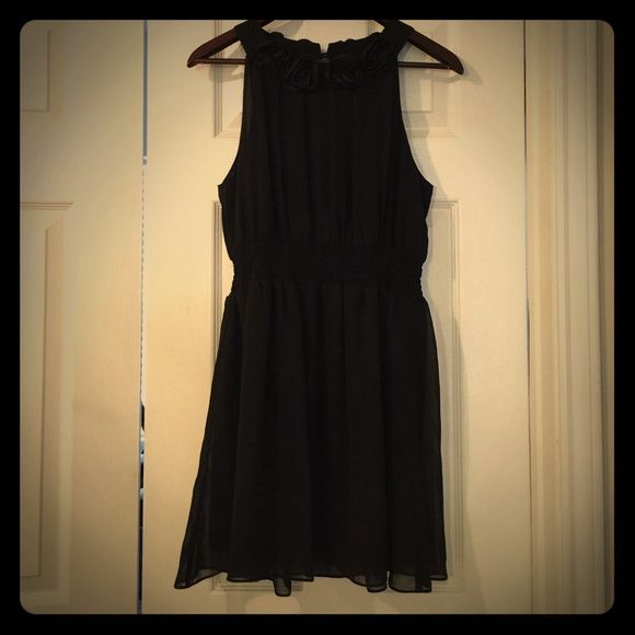 Beautiful flowy LBD with rose detail Black sleeveless flowy black dress. Rose detail around neck (front through back) keyhole opening with button closure at neck. Gathered waist. Very fun party dress for cocktail hour/holiday parties...would look adorable with booties this season! Forever 21 Dresses