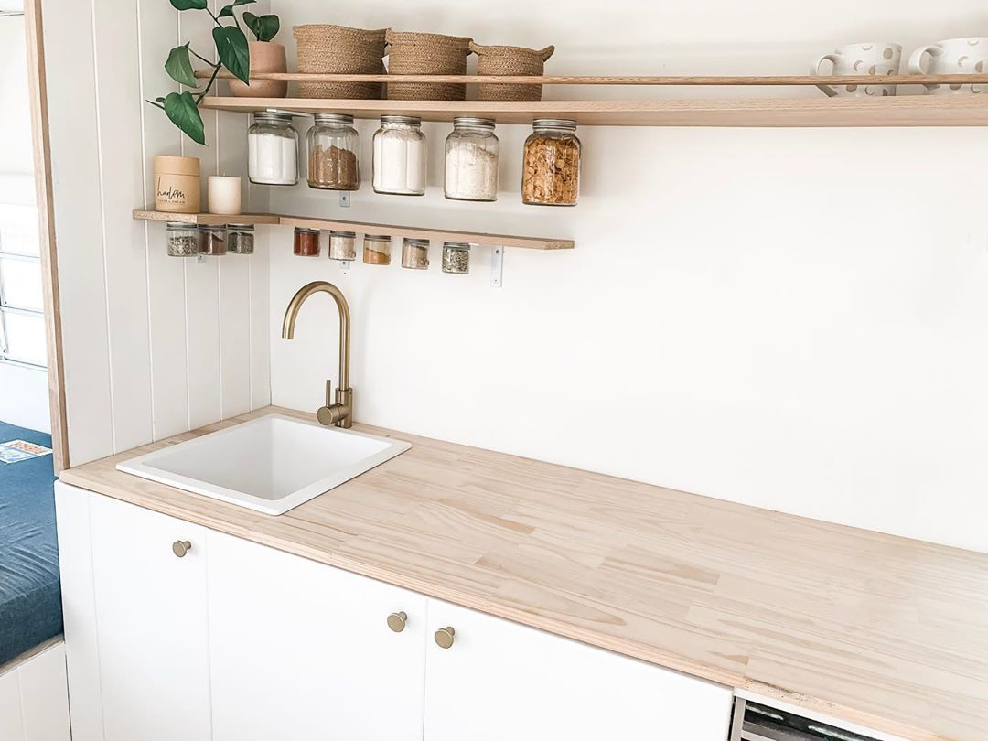 A white stone sinks works beautifully in this light wood countertop, and accented with a brass tap.
