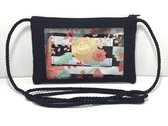 Text or email straight through the clear front of this purse and then go about your shopping with this Pink, Mint, and Gold Flowers and Stripes Text and Tote™ phone wristlet.