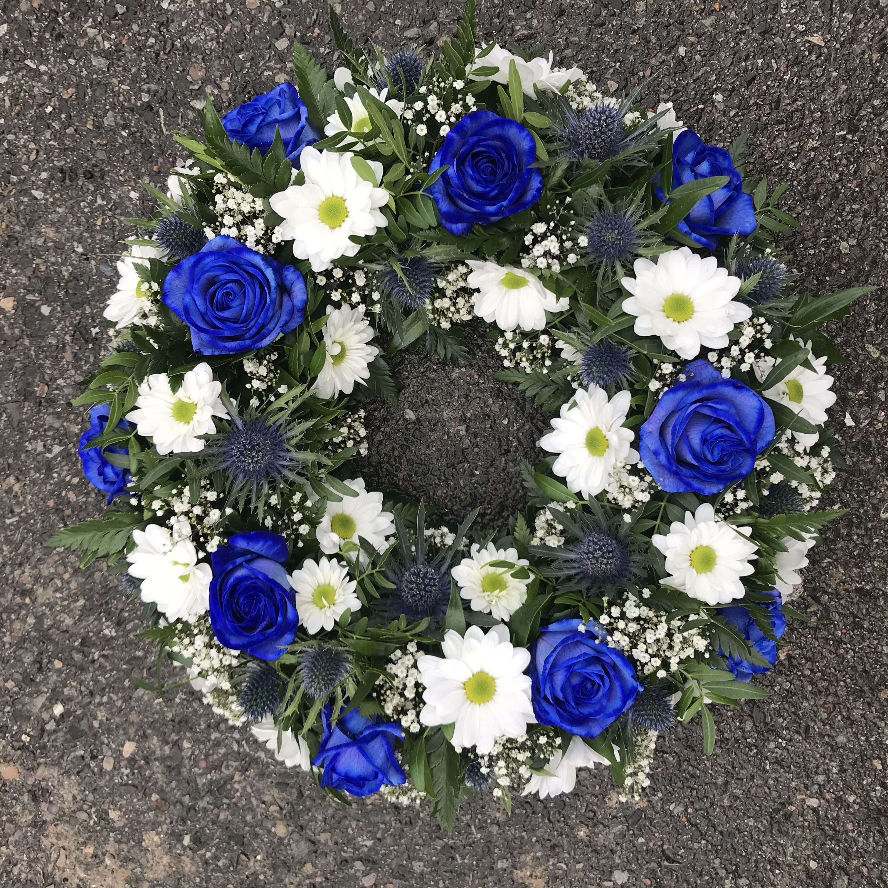 A White And Blue Funeral Floral Wreath Tribute Of Roses Thistle