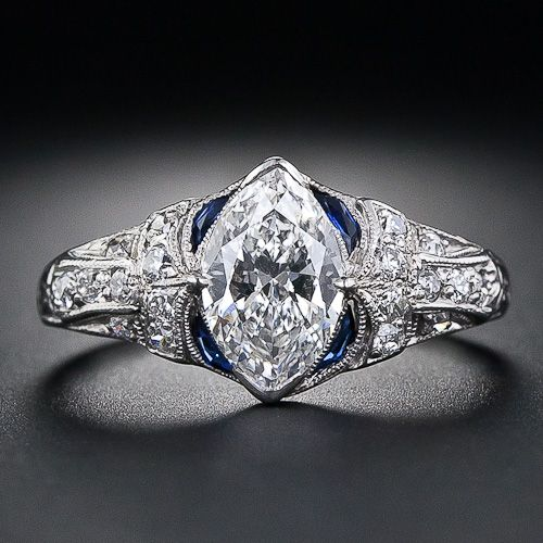 A bright & beautiful, high-color, marquise diamond, weighing 1.02 carats, sparkles mightily from the center of this sensational & highly distinctive, original Art Deco diamond ring, handcrafted in platinum. The marquise diamond is accented by four slender crescent-shape sapphires, which, although synthetic, are absolutely original to the period. The shoulders of the mounting are adorned with a striking, diamond-set geometric design, which beautifully compliments the subtle curves of the…