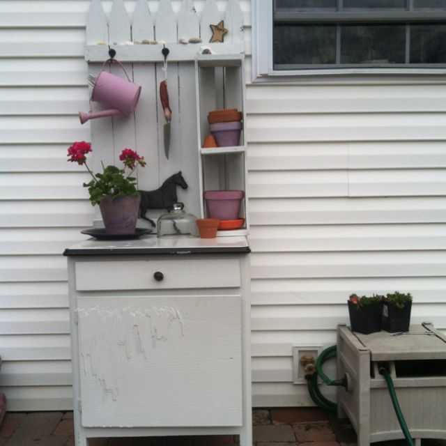 Pitting bench- old Hoosier style ceramic top cupboard + fence portion + packing box. Paint cost more than the rest put together, lol. Still needs a latch for the door. Nice and close to the hose reel. Now I have a place to pot and to keep my refreshments (I tend to forget to hydrate myself)