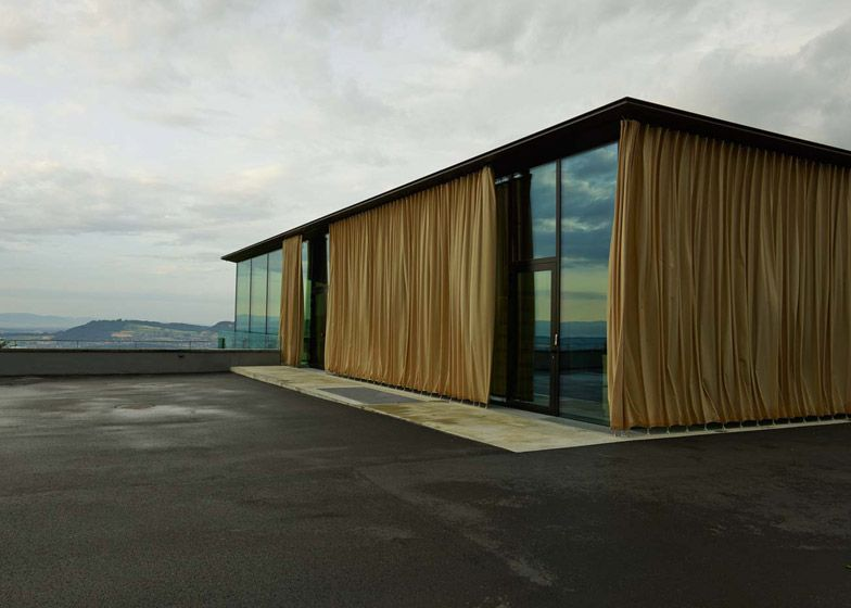 Alpine Events Venue Features Glass Walls With Golden Outdoor Curtains