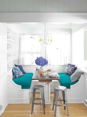 This breakfast nook gets pops of color from its upholstered bench and pillows. #decorating