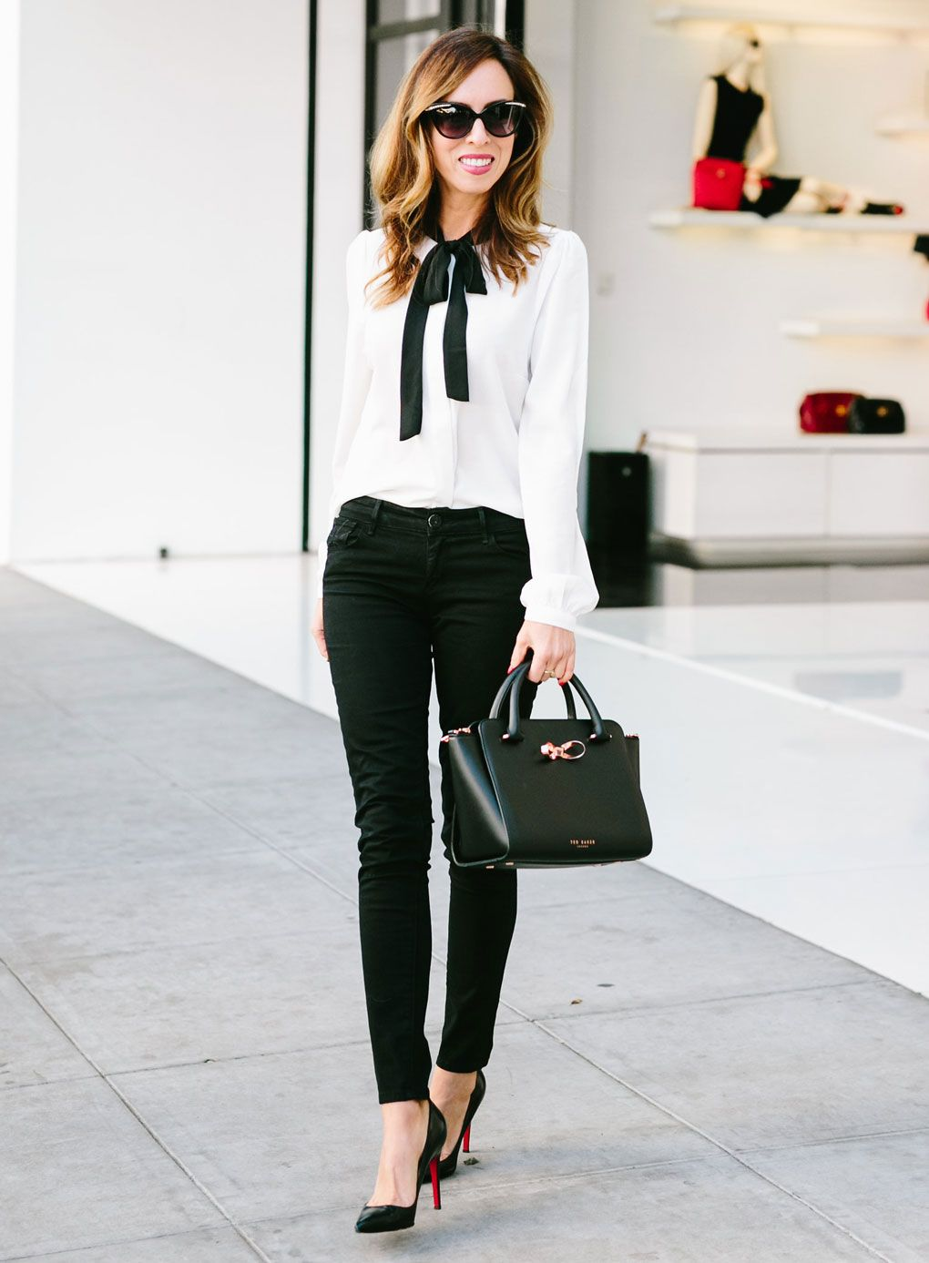 a17277637e82 Sydne Style - Los Angeles fashion blogger and People StyleWatch contributor Sydne  Summer shows how to wear black jeans with a bow blouse at the office.