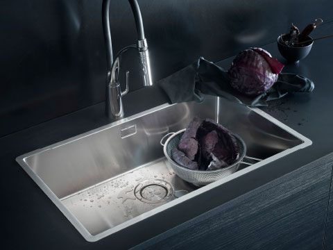 A rectangular stainless steel sink and a kitchen mixer tap with ...