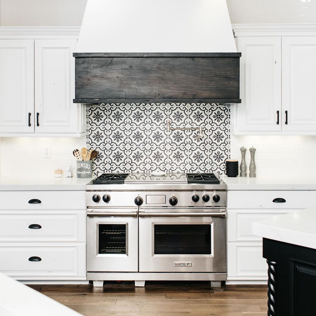 White Kitchen With Black And White Graphic Wall Tile Behind The Stove Range And A Dark Wood White Modern Kitchen Modern Kitchen Backsplash White Kitchen Decor