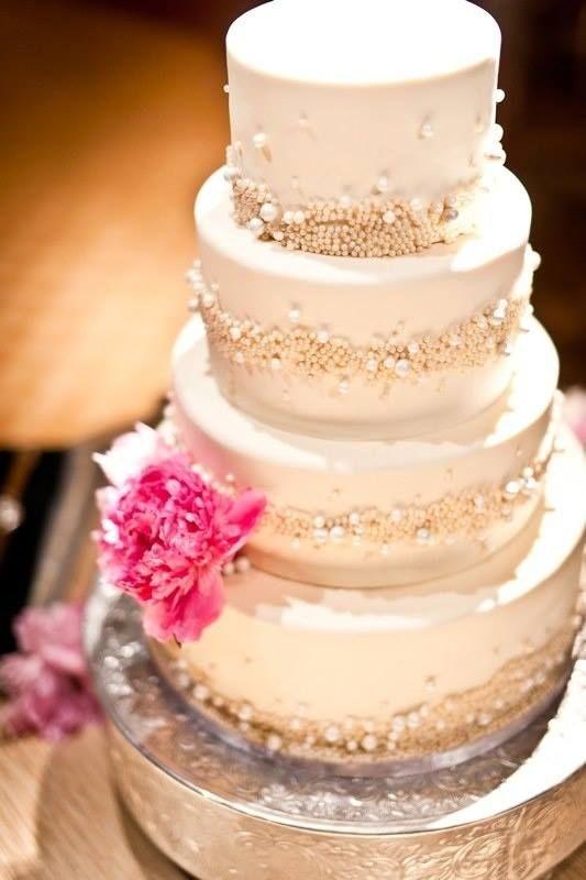 Lovely white on white  cake with small flower.  very elegant.