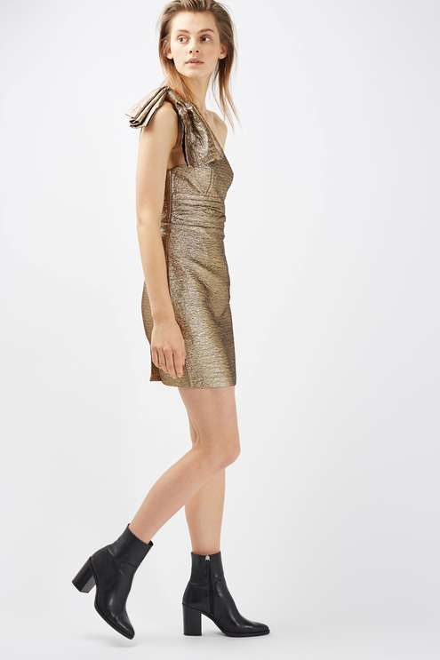 Give your partywear a new lease of life in this unique metallic gold dress with a large bow detail to one shoulder. In a mini cut, make this dress your go-to piece for the festive season. #Topshop