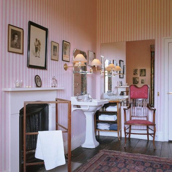 Period bathroom with pink candy striped wallpaper fireplace white basin and chair