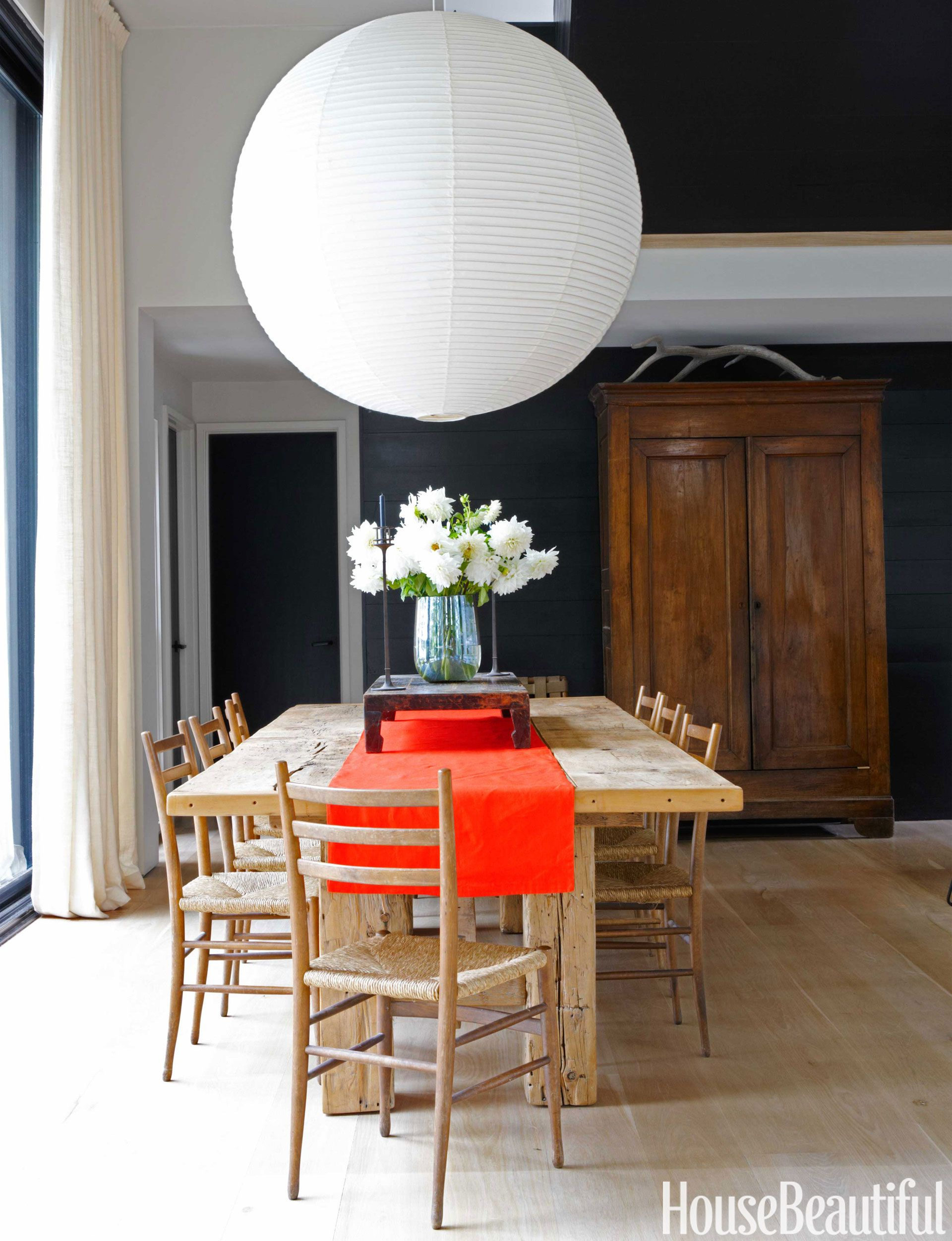The extra large akari lantern by isamu noguchi hovers like a full moon in a modern upstate new york house the paper shade casts a warm glow over the