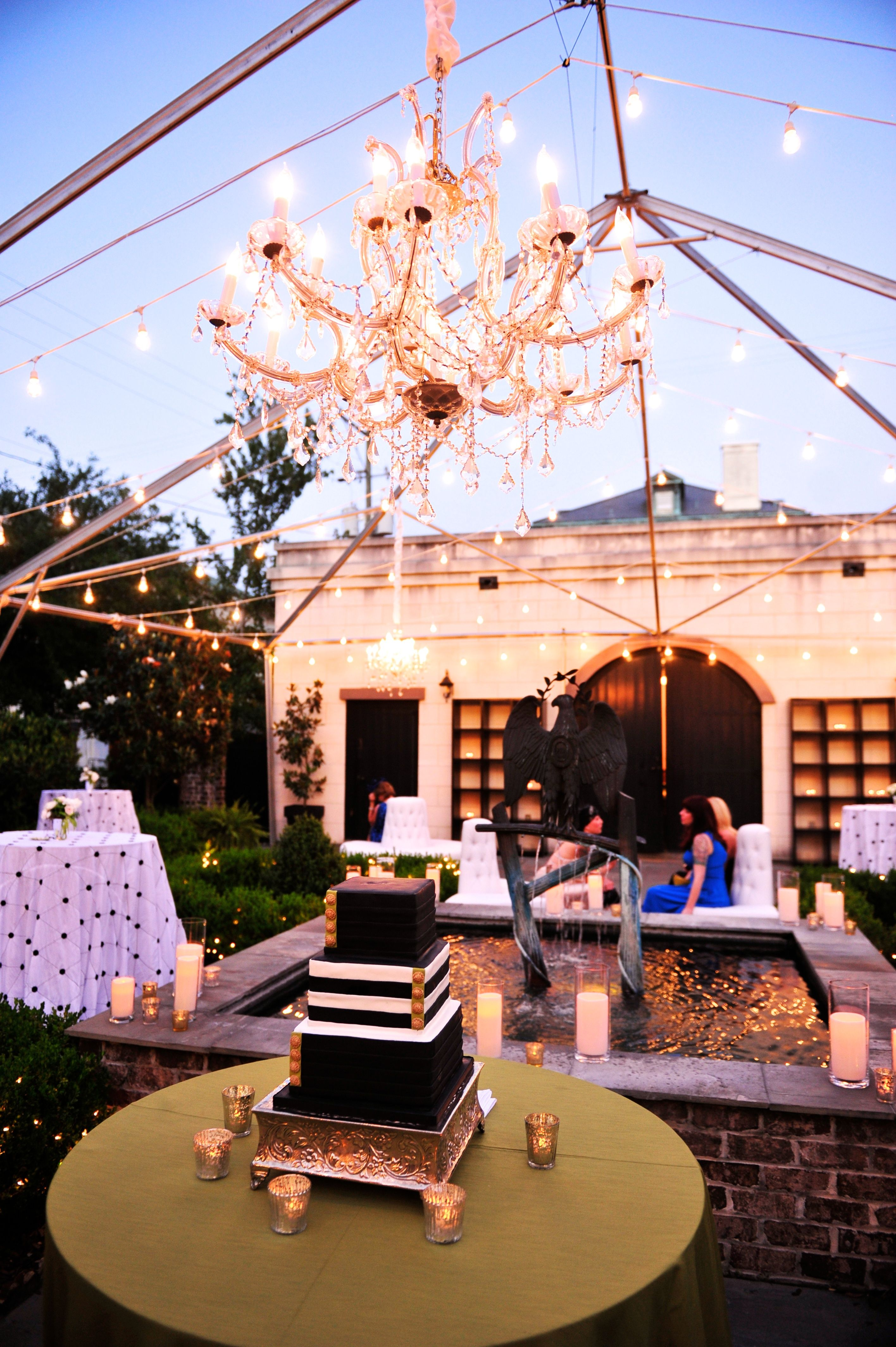 featured tent frame with chaneliers and bare bulb lighting
