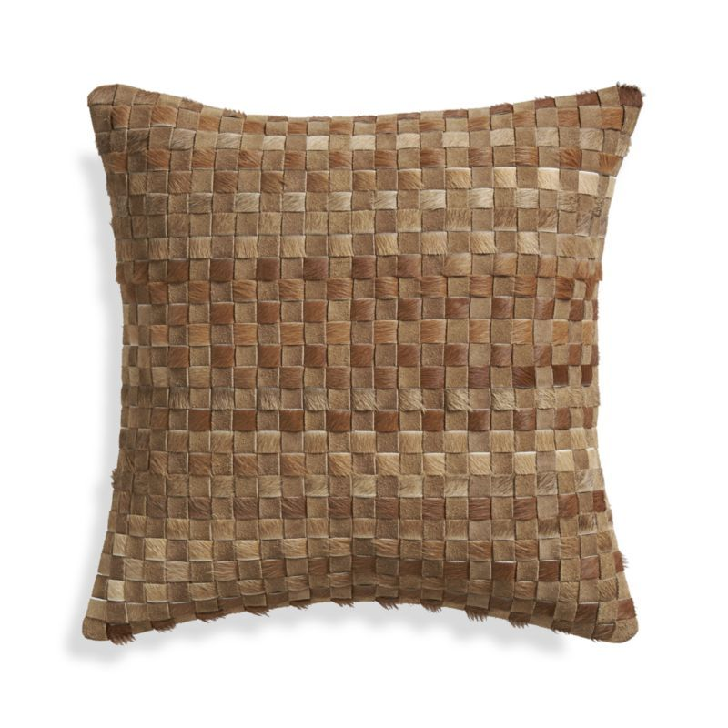 Split leather and hide strips interface in this touchable, textural pillow, bringing out the natural allure and irresistible feel of leather in a contemporary weave.  Painstakingly crafted by trained artisans, each pillow takes six to eight hours to produce.  Reverses to solid brown cotton.