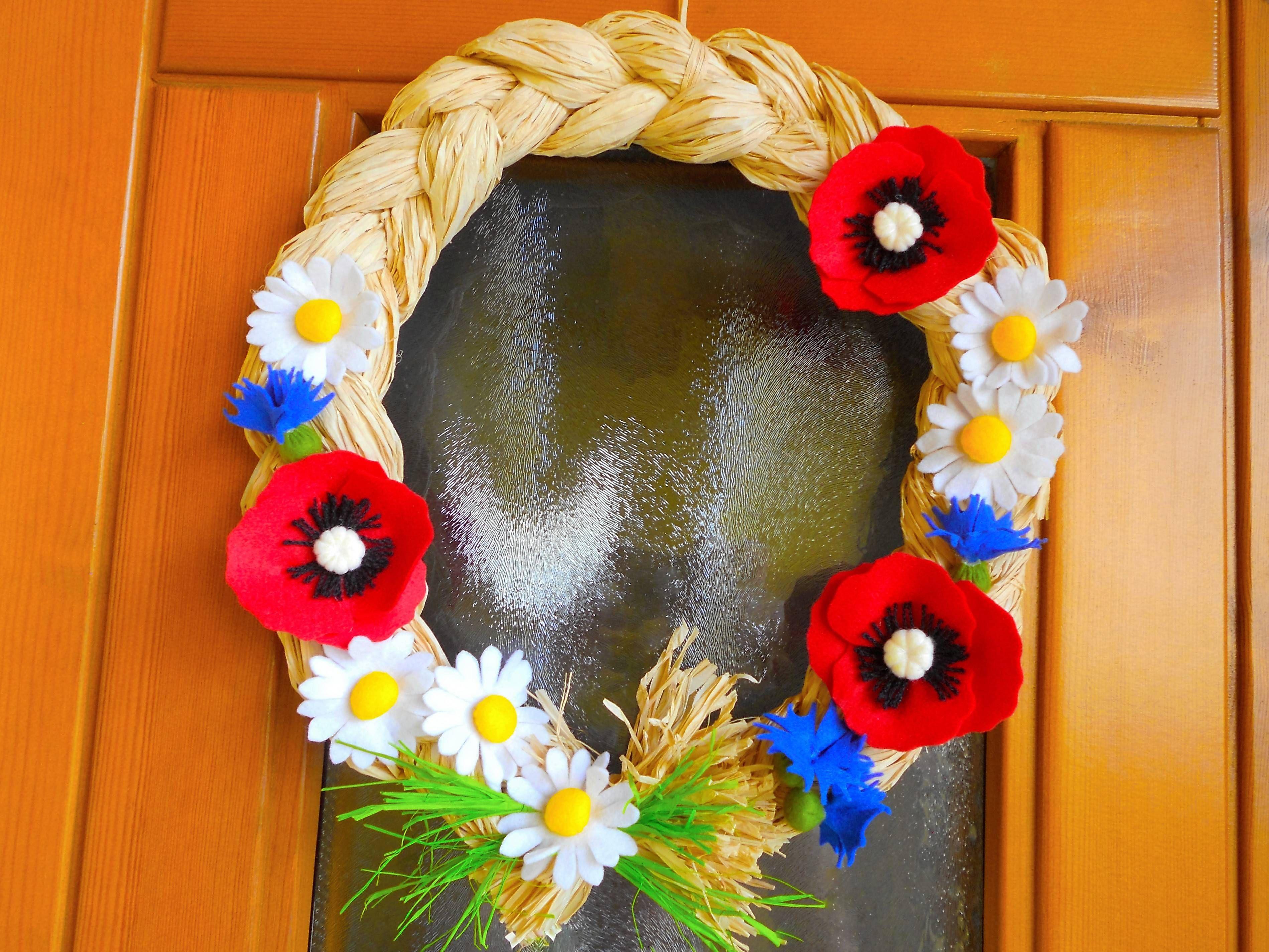 Fuoriporta estivo. Treccia di rafia decorata con papaveri, margherite e fiordalisi in pannolenci.