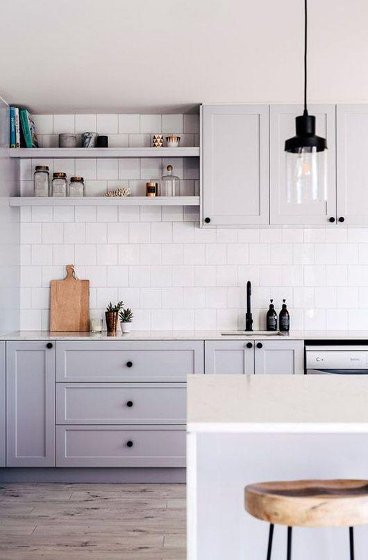 Gabinetes de cocina gris con backsplash de azulejos blancos y luces ...