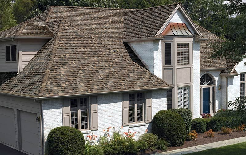 A White Brick House Shows Off The Dynamic Color Of Sand Dune Light Brown Shingles Paired With Warm Brown Roof Houses Shingle Colors Architectural Shingles Roof