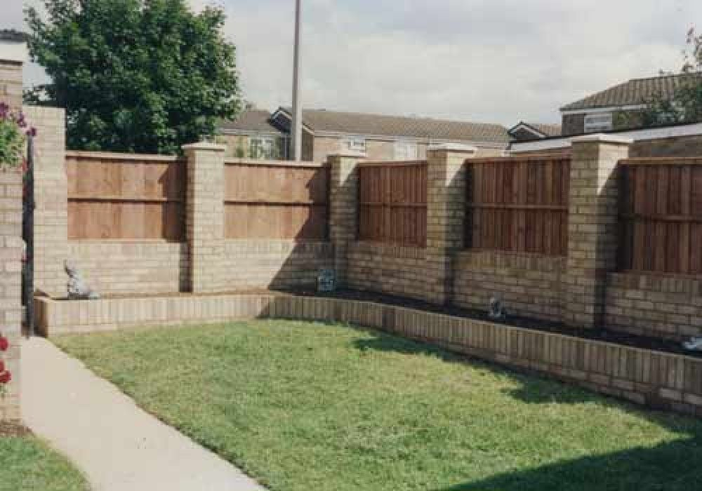 Here S A Brick Fence With Wooden Panels