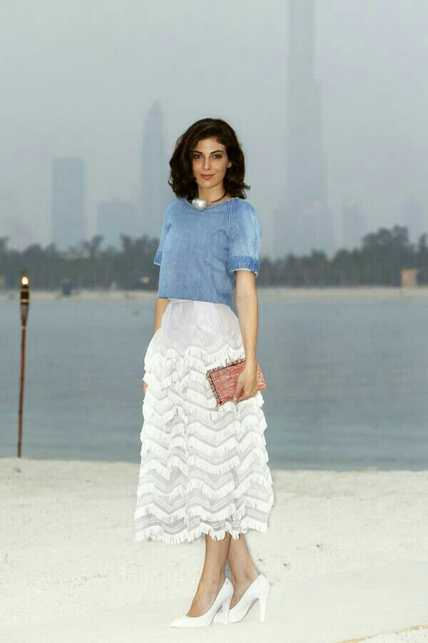 Razane Jammal wears blue denim top with white organza skirt and big single pearl necklace Chanel Cruise 2015 Front Row modest fashion