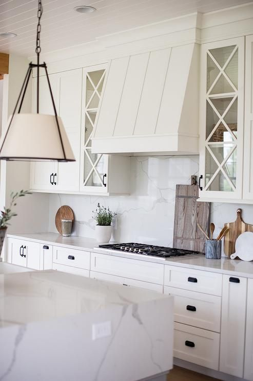Glass Mullion Kitchen Cabinets Paired With White Shakers Surround A White Vent Hood And Calcutt
