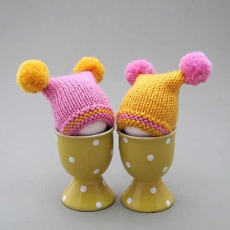 2 eggvarmere, med to pomponger, rosa og gul